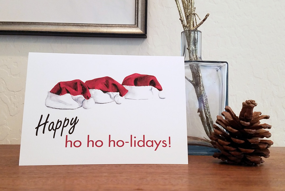 "A set of 12 watercolor painting of 3 Santa hats printed on premium cardstock with saying ""Happy ho-ho-holidays!"" on the front by artist Esther BeLer Wodrich"