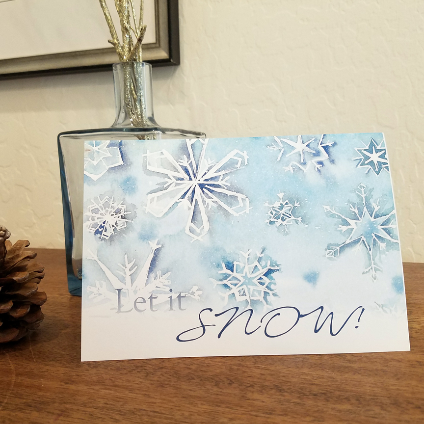 "Let it snow! Christmas card is a watercolor painting of snowflakes printed as a greeting card with message ""Let it snow!"" on the front"