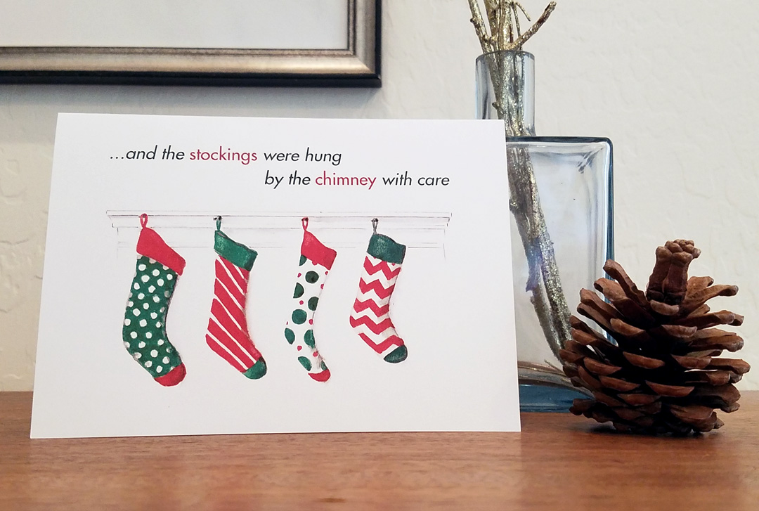 12 premium greeting cards printed with a watercolor of 4 hanging stockings on a fireplace mantle by artist Esther BeLer Wodrich